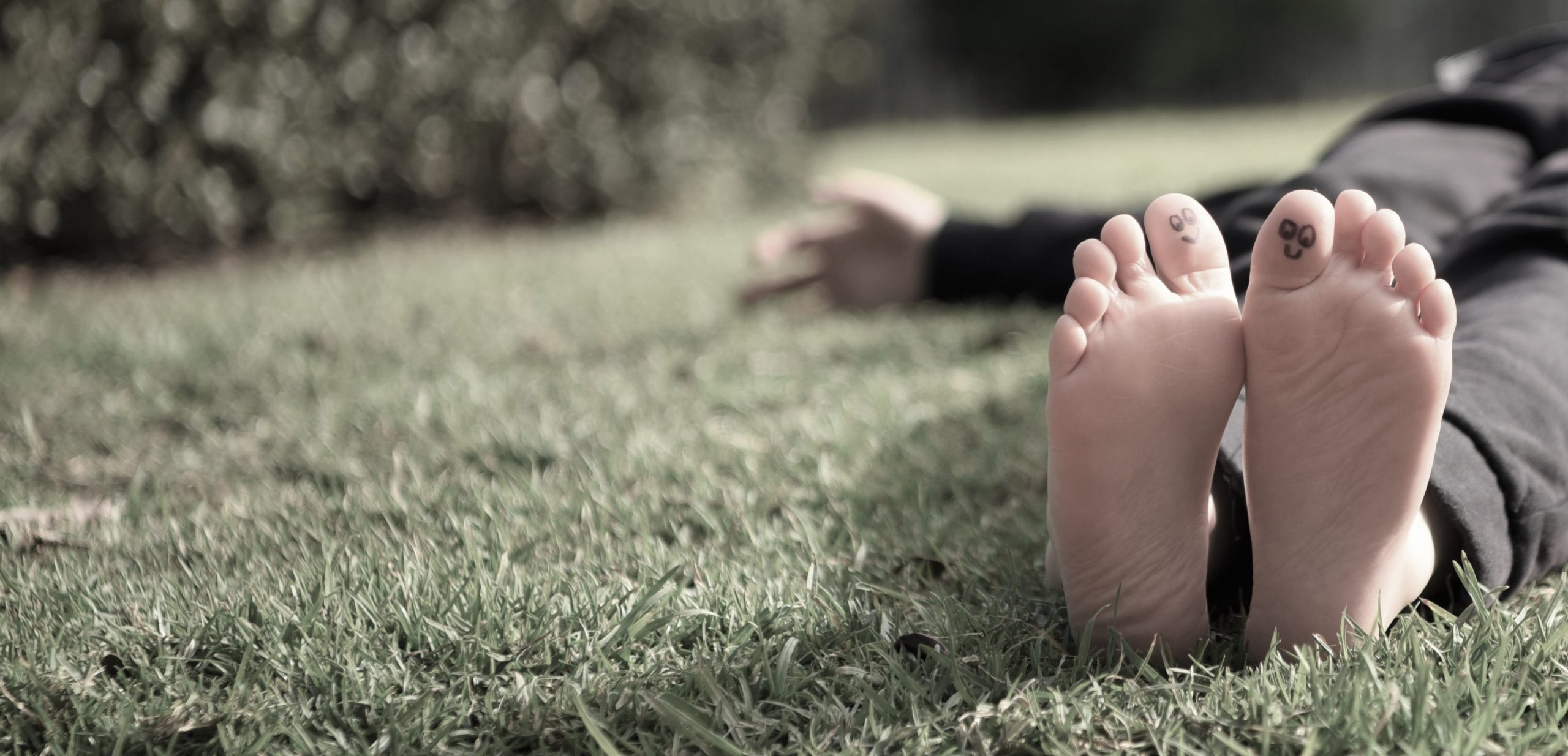 Pair of feet with smiley faces drawn on big toes, person laying on the grass